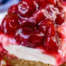 Slice of cherry delight on white plate with recipe title on top of image