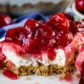 Slice of cherry delight with one bite missing on a white plate