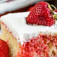 Strawberry jello poke cake slice on white plate with strawberry on top and recipe title on top of image