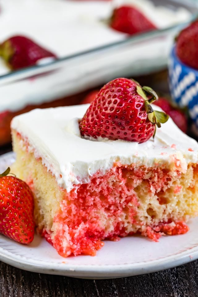 Close up of strawberry jello poke cake with a strawberry on top