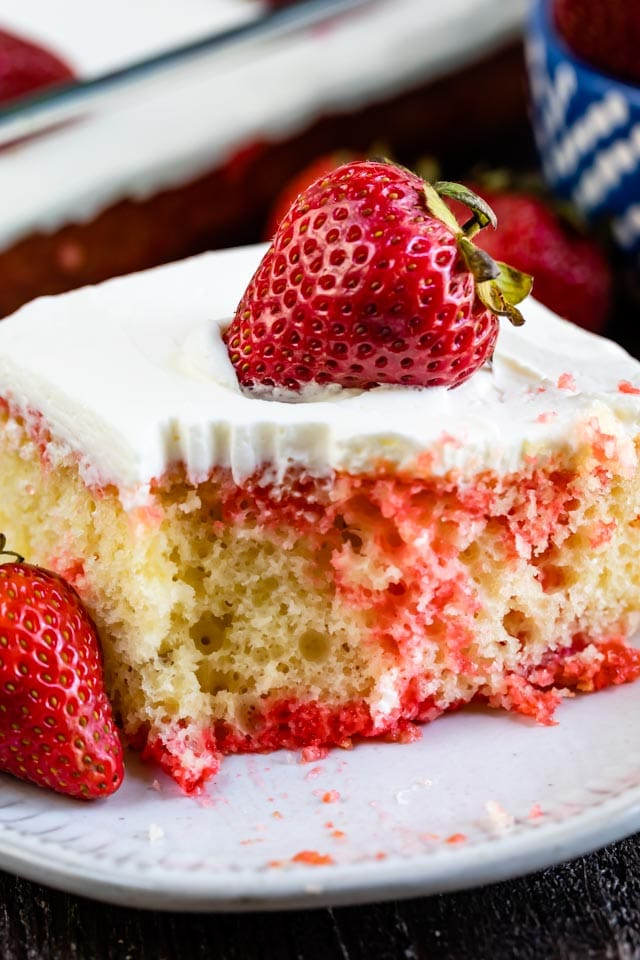 Strawberry jello poke cake on white plate with strawberry on top and one corner missing