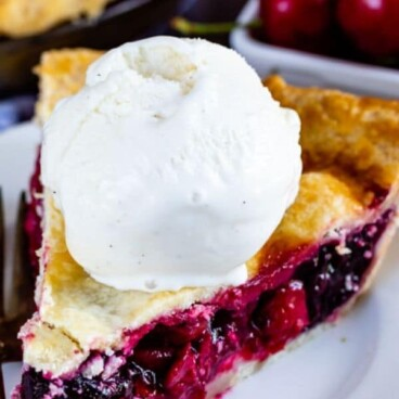 Slice of cherry pie with a scoop of ice cream on a white plate with recipe title on top of photo