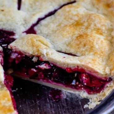 Close up shot of cherry pie with one slice missing and recipe title on top of image