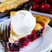Slice of cherry pie with a scoop of ice cream on top on a white plate with fork