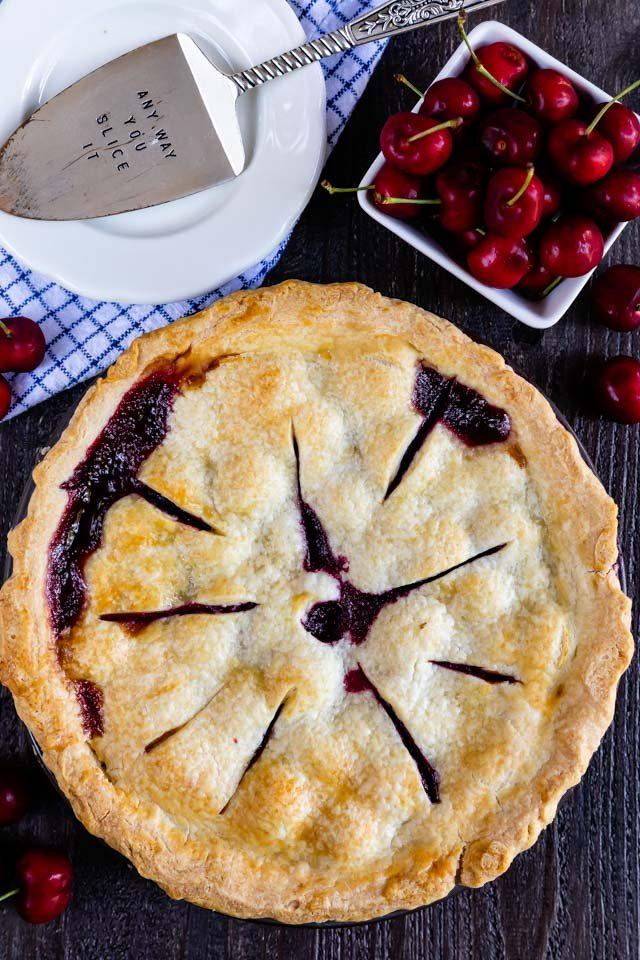 Overhead shot of full cherry pie with plate and basket of cherries on wood table
