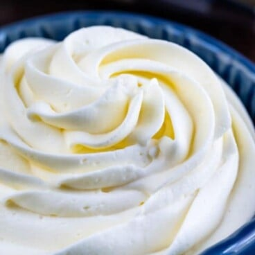 Whipped cream frosting in a blue bowl with recipe title on top