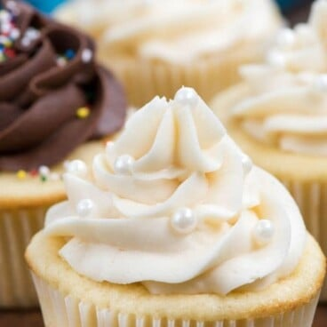 Vanilla cupcakes on wood table with vanilla buttercream frosting and recipe title on top of image