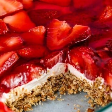 Strawberry pretzel salad in glass baking dish with one square missing with recipe title in text on top of image