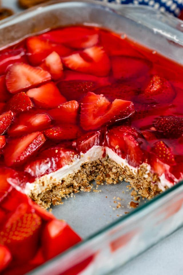 Strawberry pretzel salad in glass baking dish with one square missing