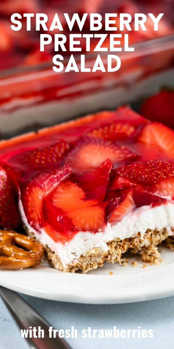 One square of strawberry pretzel salad on a white plate with recipe title in text on top of image