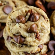 Overhead shot of chocolate chip pecan cookies stacked on a wood cutting board with chocolate chips and pecans