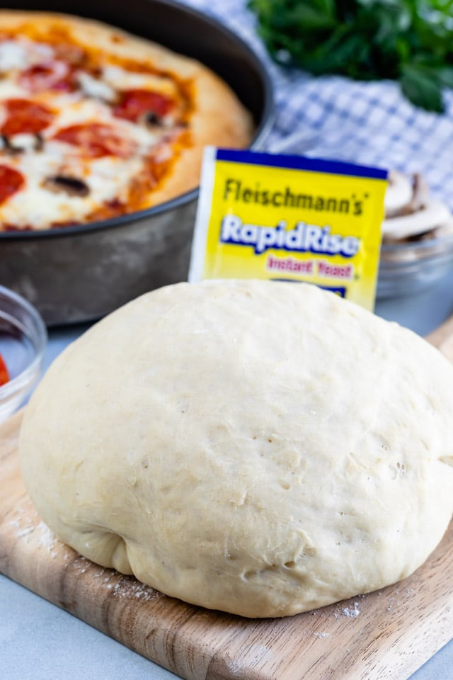 Pizza dough in a ball sitting on a wood cutting board with yeast packet and deep dish pizza in background