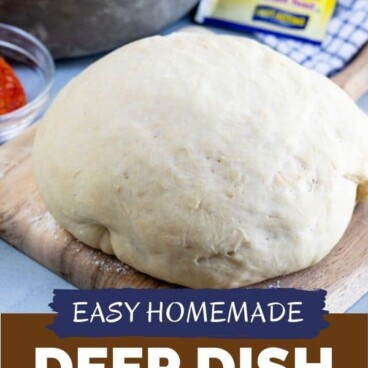 Pizza dough in a ball sitting on a wood cutting board with yeast packet and deep dish pizza in background with recipe title on bottom of image