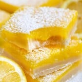 Stack of the best lemon bars with powdered sugar on top and one bite missing