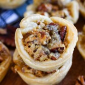 Close up shot of mini pecan pies stacked on top of eachother on cutting board
