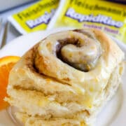 Close up of an orange sweet roll on a white plate with yeast packets behind it
