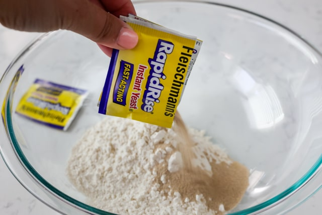 Instant yeast being poured into glass mixing bowl