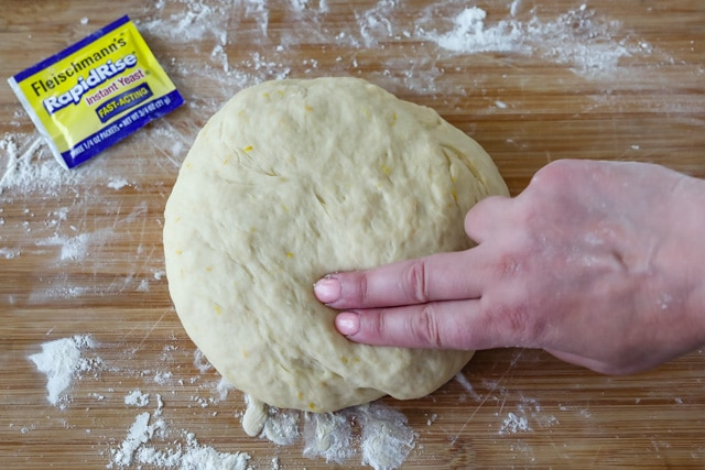 Overhead shot of dough being pressed in to with two fingers and instant yeast packet beside it