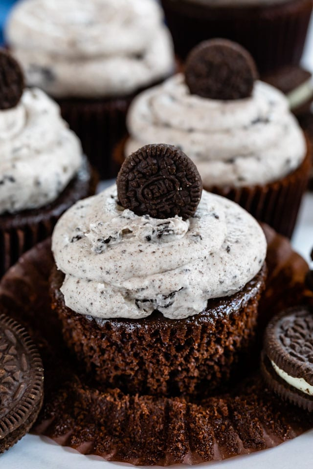Close up of unwrapped oreo cupcake with buttercream icing and mini oreo on top