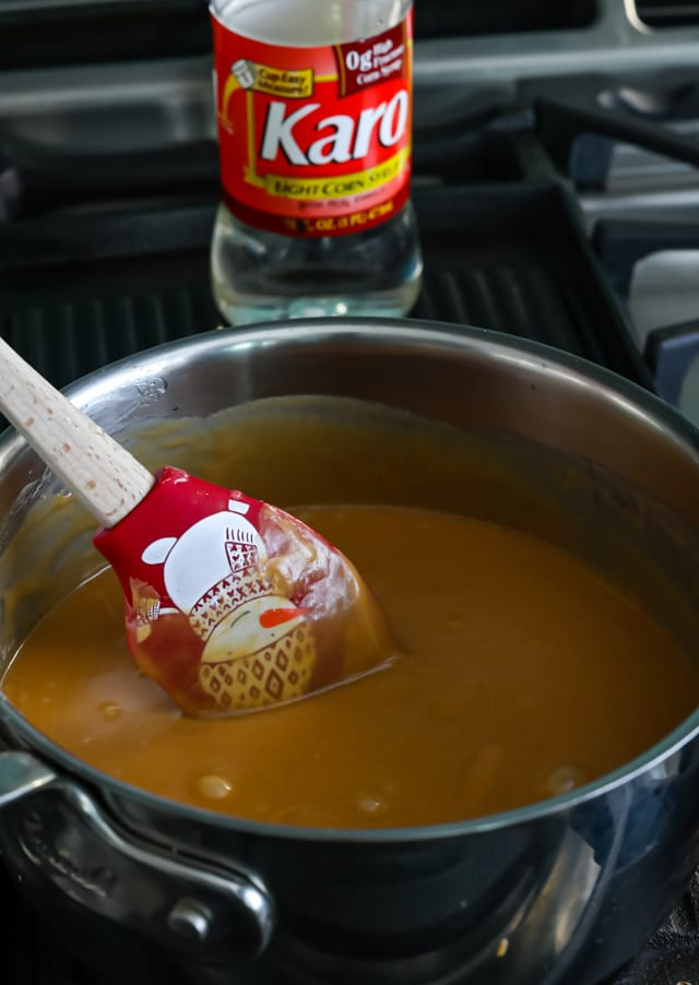Corn syrup and peanut butter mixed together in pot on stove with red holiday spatula