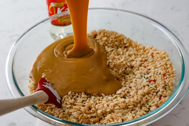 Peanut butter mixture being poured into glass mixing bowl with rice cereal and sprinkles