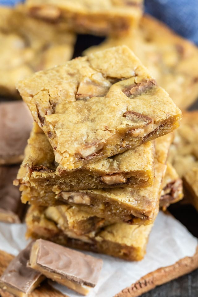 Overhead view of stacked toffee blondies with bits of toffee around
