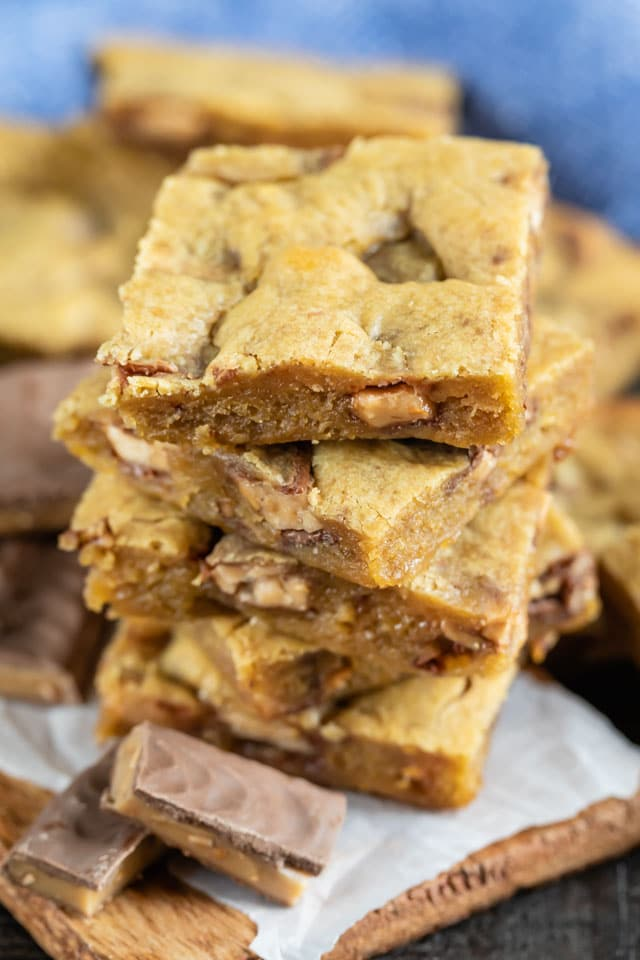 Close up photo of toffee blondies stacked on top of eachother with toffee bits on table