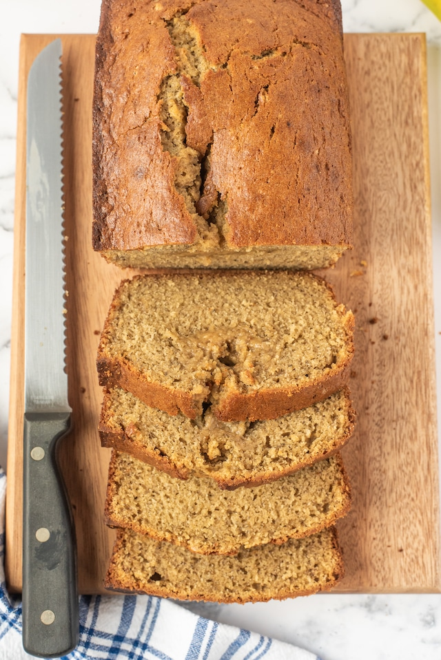Overhead shot of banana bread loaf half sliced on a cutting board with bread knife