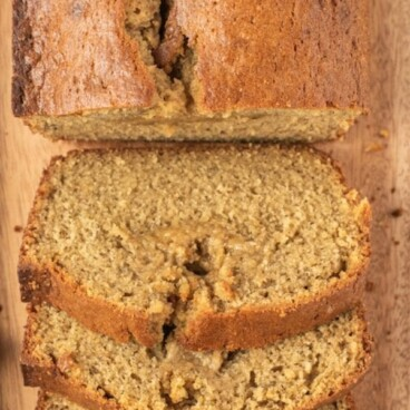 Overhead shot of biscoff banana bread loaf half sliced on wood cutting board with recipe title on top