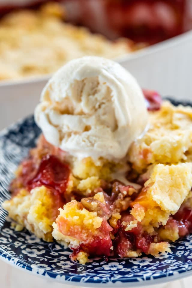 dump cake with cherries on blue patterned plate with ice cream