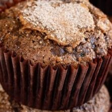 Two chocolate zucchini muffins stacked with recipe title on top