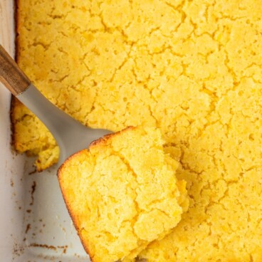 Overhead shot of jiffy corn casserole in a white baking dish with one corner piece being lifted out of dish