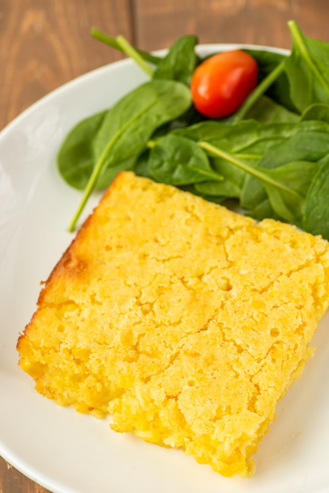 Close up of a piece of weight watchers corn casserole on a white plate with side salad next to it