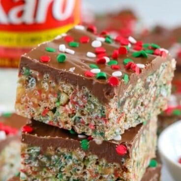 Three holiday no bake cereal bars stacked on top of eachother with corn syrup bottle in background