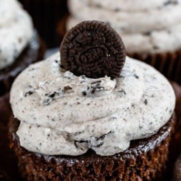 Close up of unwrapped oreo cupcake with buttercream icing and mini oreo on top with recipe title on top