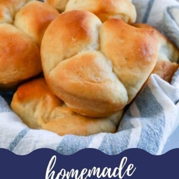 Close up of cloverleaf dinner rolls in a roll basket with recipe title on bottom of image
