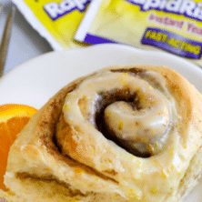 Close up photo of one orange sweet roll on a white plate with yeast packets in background with recipe title on top