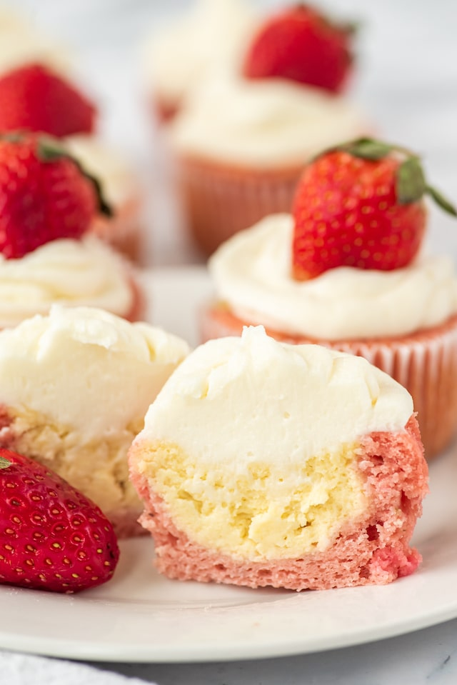 Strawberry cheesecake cupcakes on a white plate with front cupcake cut in half to show cheesecake filling