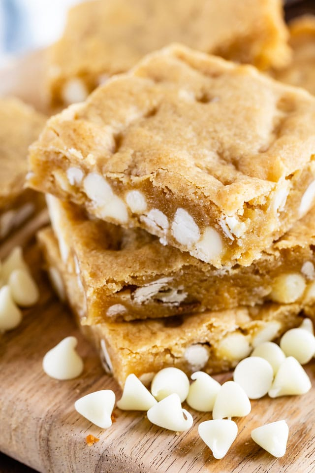 Stack of white chocolate blondies on a cutting board with white chocolate chips scattered around