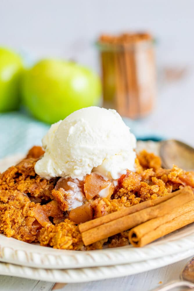 Apple dump cake on a white plate with a scoop of ice cream on top