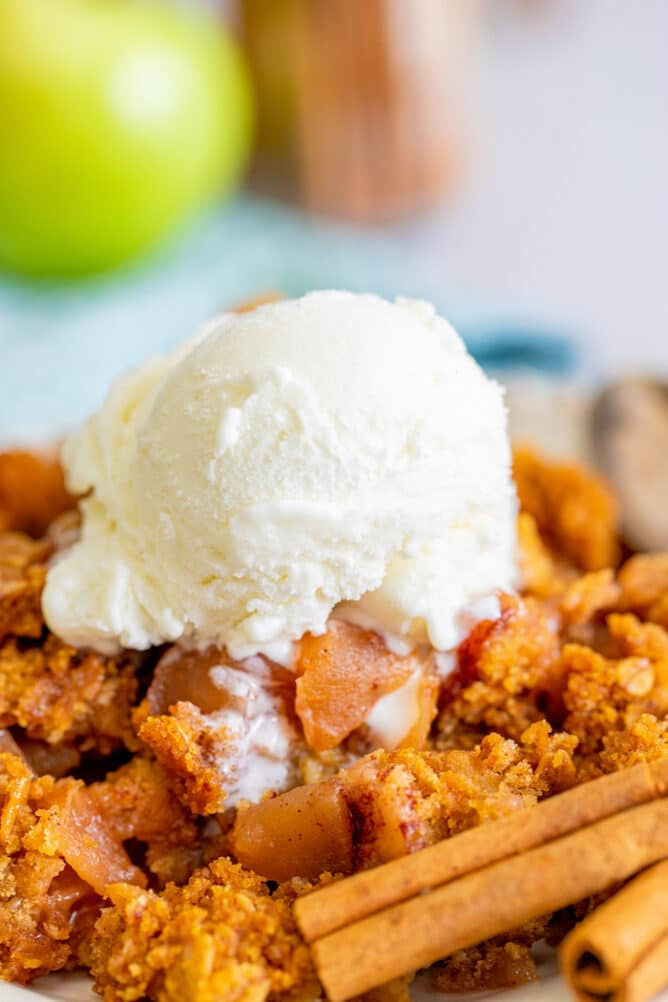 Close up shot of apple dump cake on plate with vanilla ice cream on top