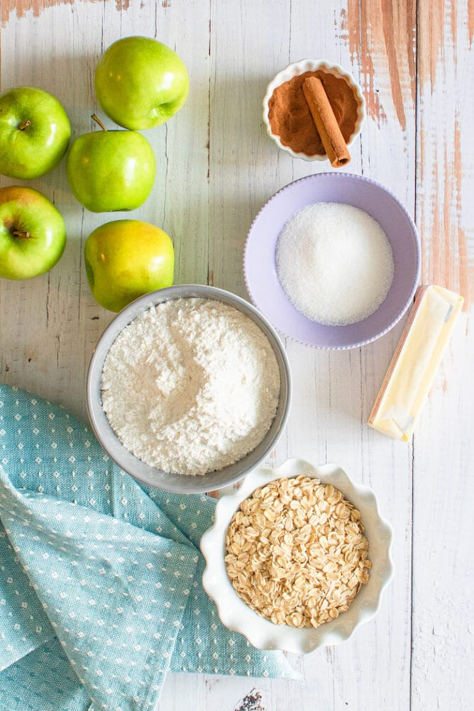 Overhead shot of apple dump cake ingredients in bowls on a wooden table