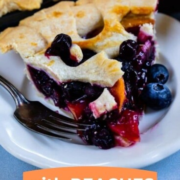 Close up shot of peach blueberry pie slice on a white plate with recipe title on bottom of photo in a color block