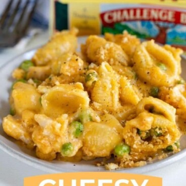 Easy cheesy chicken casserole on a grey place with challenge butter in background with recipe title on bottom of photo