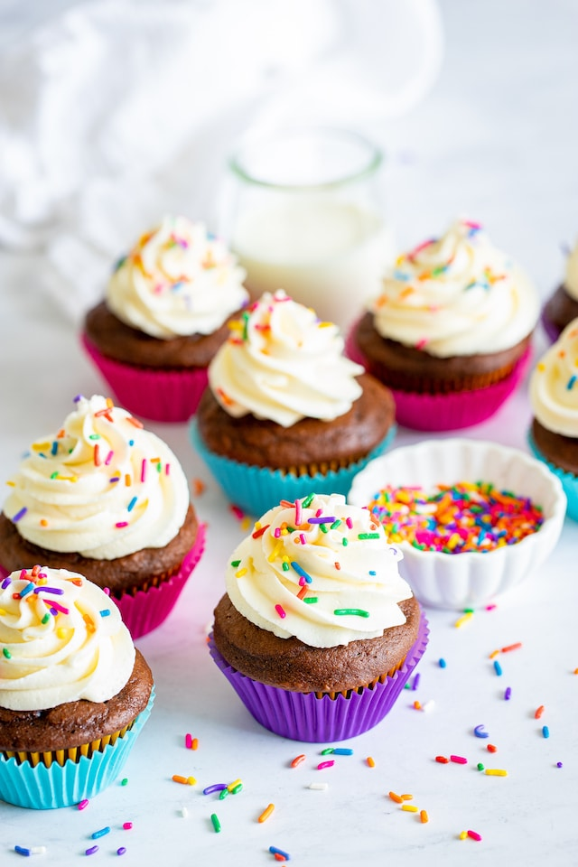 chocolate cupcakes with vanilla frosting and sprinkles on white background