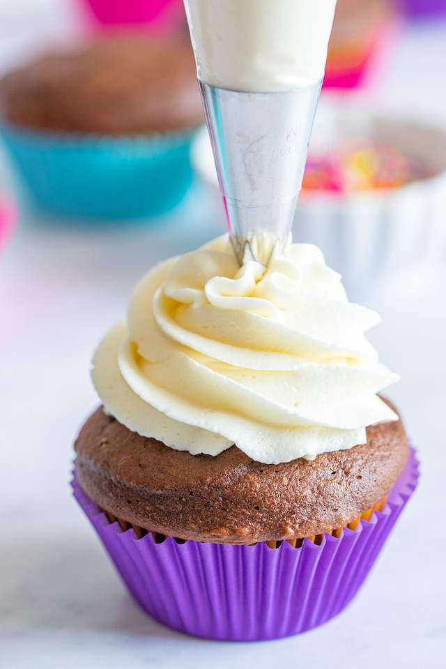 chocolate cupcake in purple liner being frosted