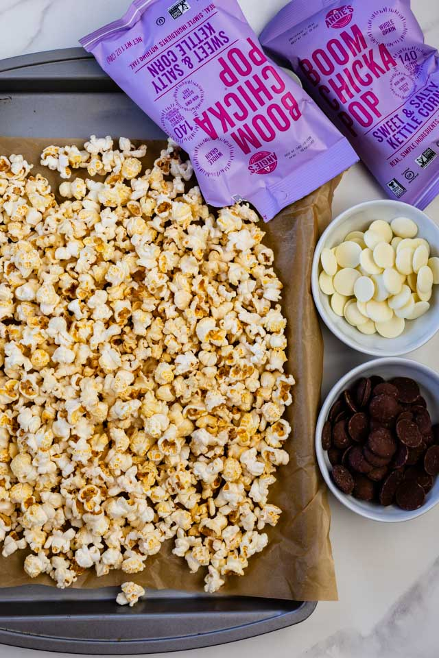 overhead photo of kettle corn on cookie sheet with bowls of chocolate and bags of Boom Chicka Pop