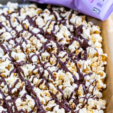popcorn covered in chocolate on cookie sheet with popcorn bag behind