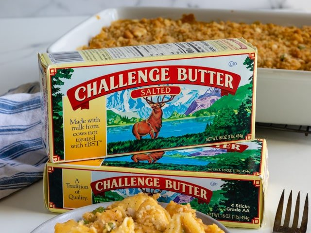 Two challenge butter boxes stacked on eachother with cheesy chicken casserole in background