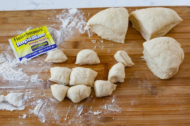 cutting board with pieces of dough
